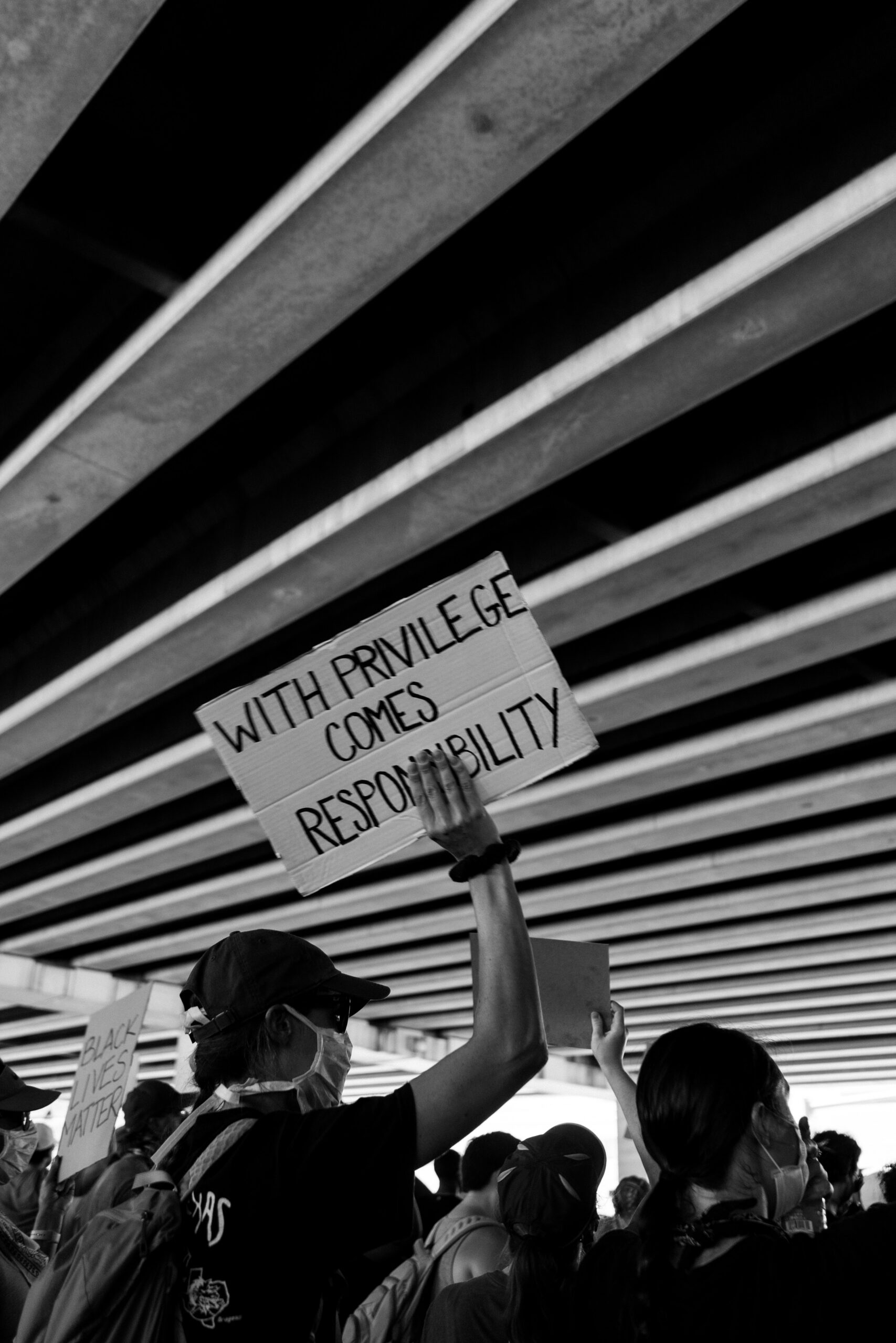 Protestor holding sign reading